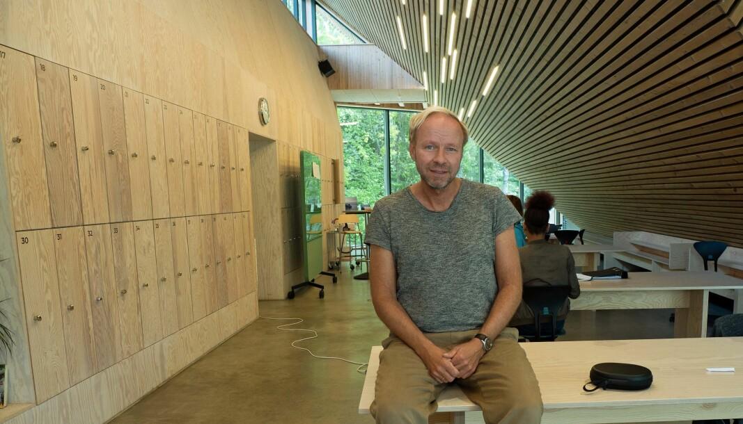 SOLSKIVE: På innsiden av den hellende «solskiven» er det blant blitt et stort felleslokale som brukes til både arbeid og spisesal, viser rektor Henning Johannessen.