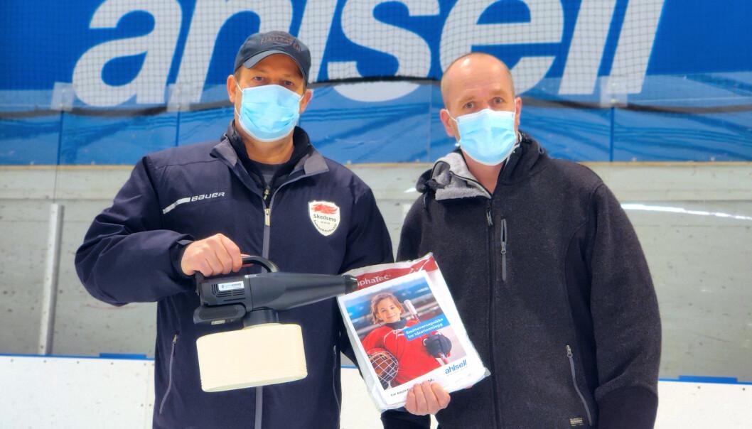Ahlsell donerer en smittevernspakke til alle landets ishaller, i håp om å holde hallene åpne så lenge som mulig. Her har daglig leder i Skedsmo Ishockeyklubb, John Obstfelder, mottatt en foggermaskin fra Vegar Carlson i Ahlsell Norge.